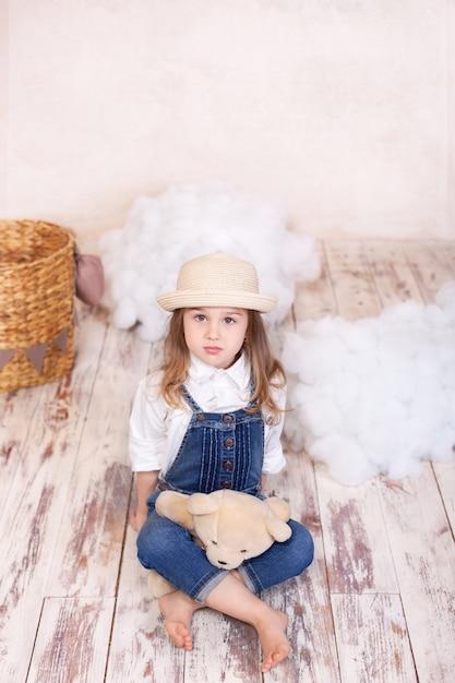 Cute Little Girl Siedzi Na Podłodze I Przytrzymaj Misia. Dziewczynka Bawi Się W Pokoju Dziecięcym Zabawką. Premium Zdjęcia