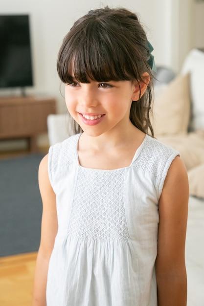 Cute Little Girl W Białej Sukni Stojąc I Uśmiechając Się W Salonie. Darmowe Zdjęcia