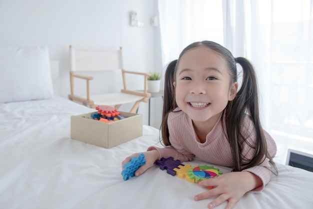 Cute Little Indian / Asian Girl Korzystających Podczas Zabawy Z Zabawkami Lub Klockami Premium Zdjęcia