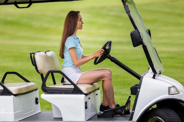 Cute młoda dziewczyna jazdy wózkiem golfowym Darmowe Zdjęcia