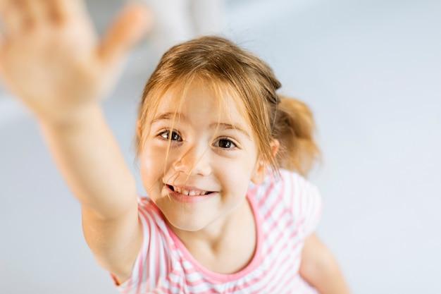 Cute Smiley Dziewczynka Podnosi Rękę Do Przodu Premium Zdjęcia