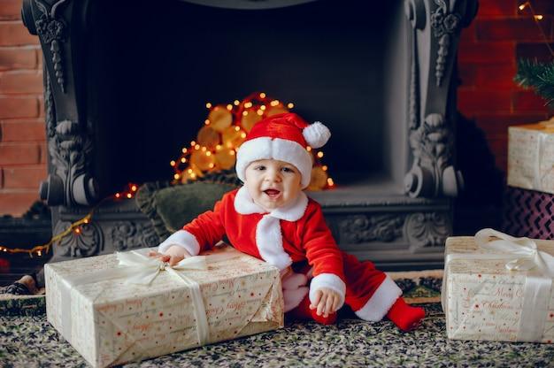 Cutte mały chłopiec w domu w pobliżu ozdób choinkowych Darmowe Zdjęcia