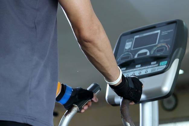 Ćwiczenia na siłowni, man walking na bieżni. Premium Zdjęcia