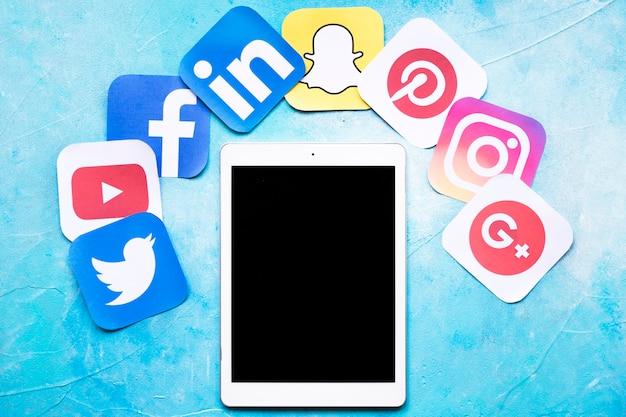 Cyfrowe Tabletki Wokół Kolorowe Ikony Mediów Społecznych Na Malowane Niebieskie Tło Darmowe Zdjęcia