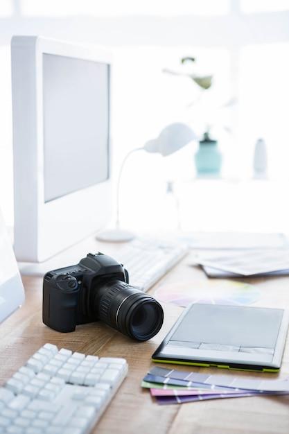 Cyfrowy aparat fotograficzny i kolorowe próbki na biurku Premium Zdjęcia