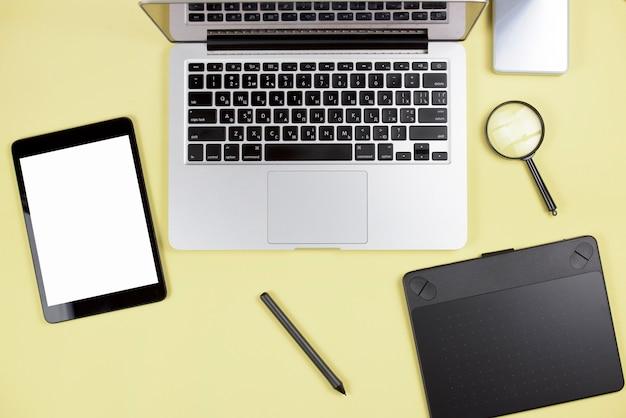 Cyfrowy tablet; rysik; graficzny cyfrowy tablet; laptop i szkło powiększające na żółtym tle Darmowe Zdjęcia