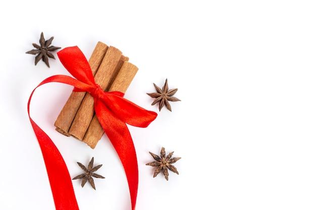 Cynamon Z Czerwoną Kokardą I Anyżem Na Białym. świąteczny Nastrój. Copysapce. Premium Zdjęcia