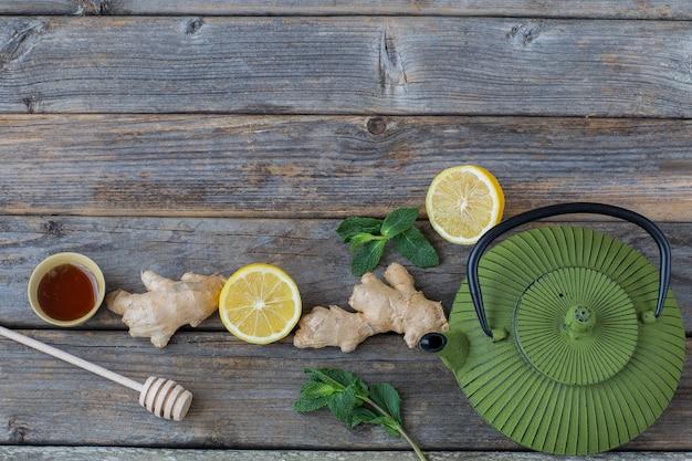 Czajnik, cytryna, miód, liście mięty i imbir na drewnianym stole - zdrowy styl życia Premium Zdjęcia