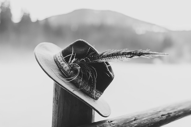 Czapka Z Piórkami Wykonana Ręcznie Na Drewnianym Płocie. ścieśniać. Czarno-białe Zdjęcie. Premium Zdjęcia