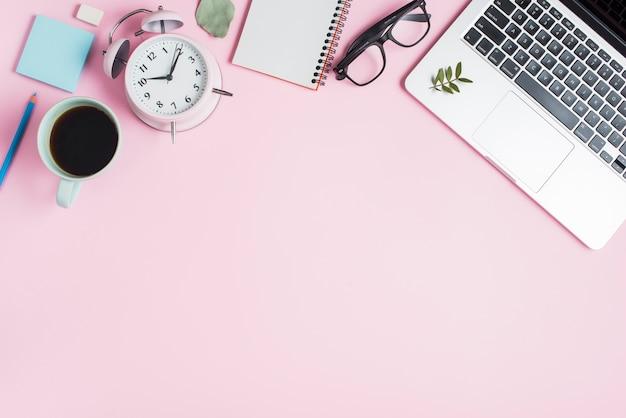 Czarna filiżanka herbaty; budzik; notes spiralny; okulary i laptop na różowym tle Darmowe Zdjęcia