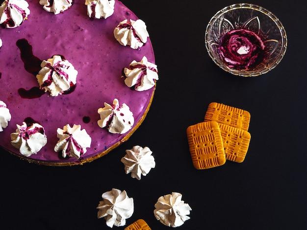 Czarna jagoda tort z marshmallow na wierzchołku i ciastkami na zmroku stole Premium Zdjęcia