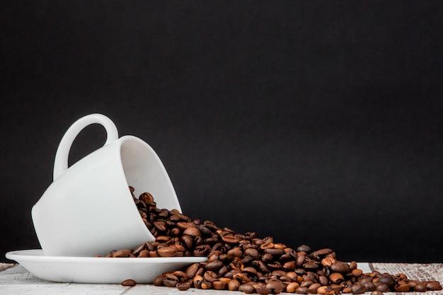 Czarna kawa w białej filiżance i ziaren kawy. copyspace Premium Zdjęcia