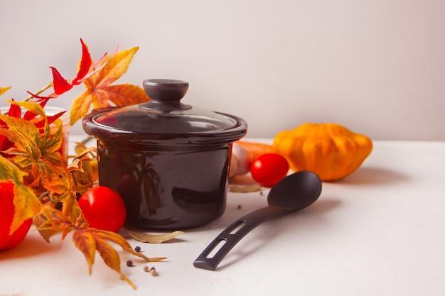 Czarna niecka z jesieni liśćmi i warzywami na białym tle Premium Zdjęcia