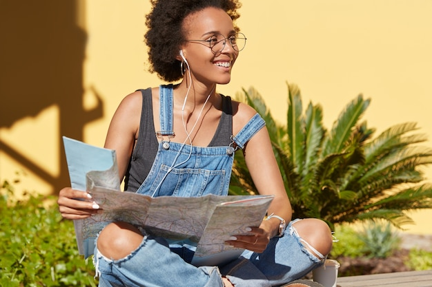 Czarna Usatysfakcjonowana Podróżniczka Afroamerykanka Korzysta Z Mapy Celu Do Wyszukiwania Interesujących Miejsc, Szuka Zwiedzania W Nieznanym Miejscu, Słucha Audycji Radiowych W Słuchawkach, Pozuje Na świeżym Powietrzu Darmowe Zdjęcia