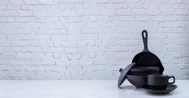 Czarne Naczynia Kuchenne Na Białej Cegły ściany Tekstury Premium Zdjęcia