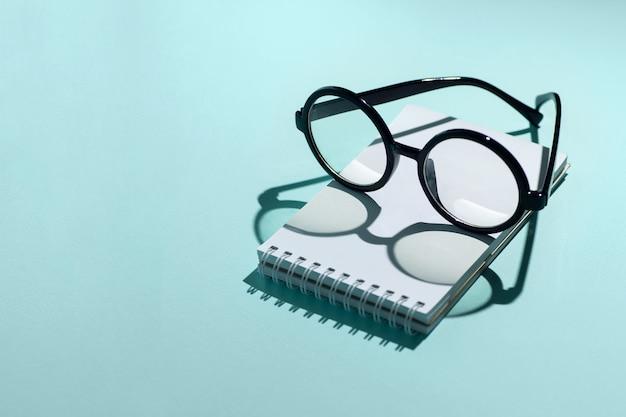 Czarne okrągłe okulary leżą na notatniku i rzucają cień Premium Zdjęcia