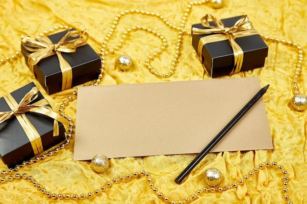 Czarne pudełka na prezenty ze złotą wstążką i pustym arkuszem papieru Premium Zdjęcia