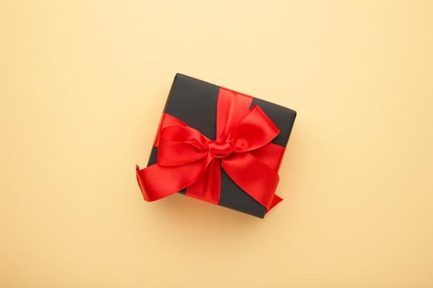 Czarne pudełko z czerwoną wstążką i beżową kokardką. Premium Zdjęcia