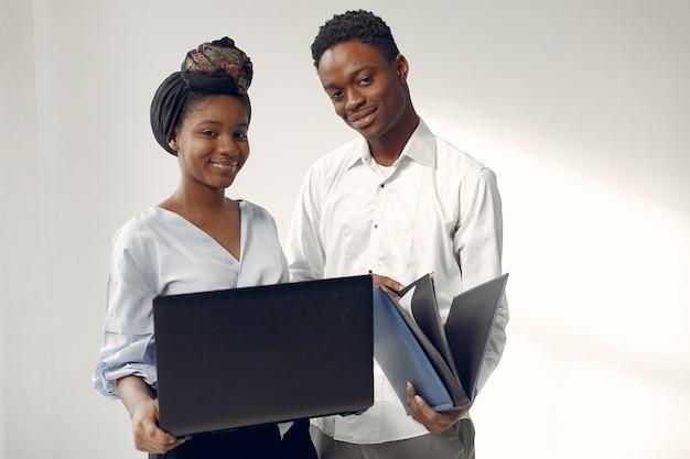 Czarni Ludzie Stojący Na Białej ścianie Z Laptopem Darmowe Zdjęcia