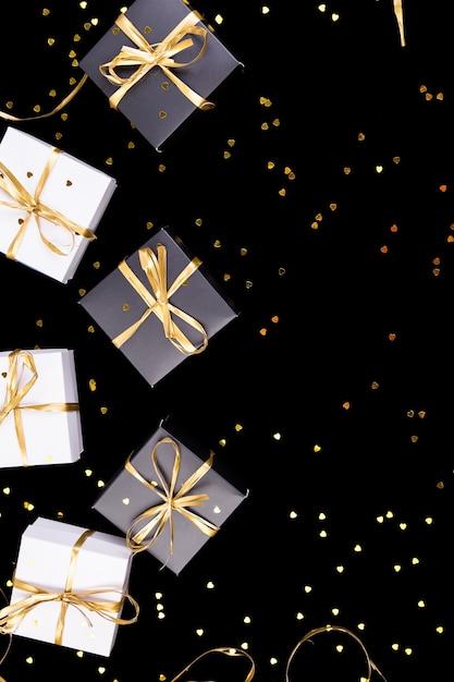 Czarno-białe Pudełka Na Prezenty Ze Złotą Wstążką Na Tle Blasku Premium Zdjęcia