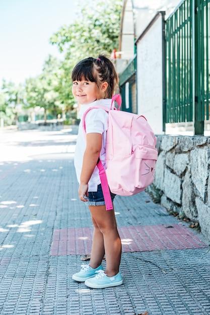 Czarnowłosa Dziewczynka Ubrana W Różowy Plecak Na Ulicy Premium Zdjęcia