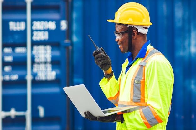 Czarny Afrykański Szczęśliwy Pracownik Pracujący W Komunikacji Logistycznej Za Pomocą Radia Premium Zdjęcia