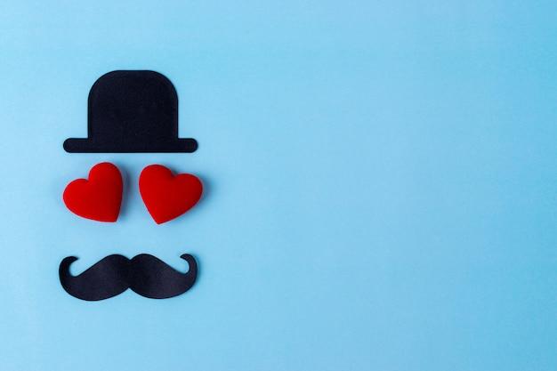 Czarny kapelusz, wąsy i dwa czerwone serce z pastelowym niebieskim tle. Premium Zdjęcia
