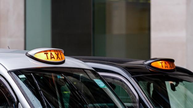 Czarny Londyński Czarny Taksówka Znak Z Niewyraźne Budynków Premium Zdjęcia