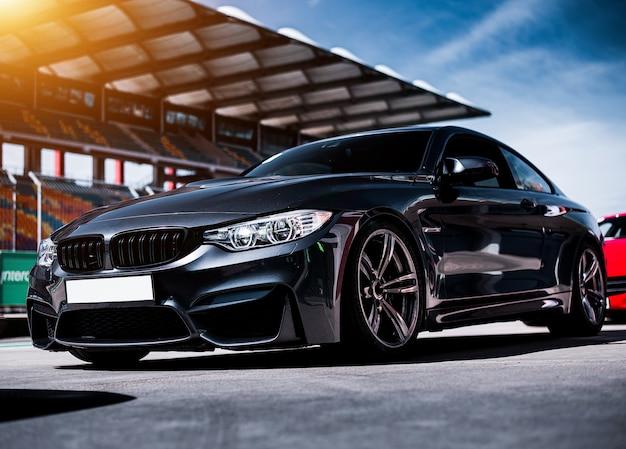 Czarny luksusowy sportowy sedan samochód stojący na torze wyścigowym Darmowe Zdjęcia