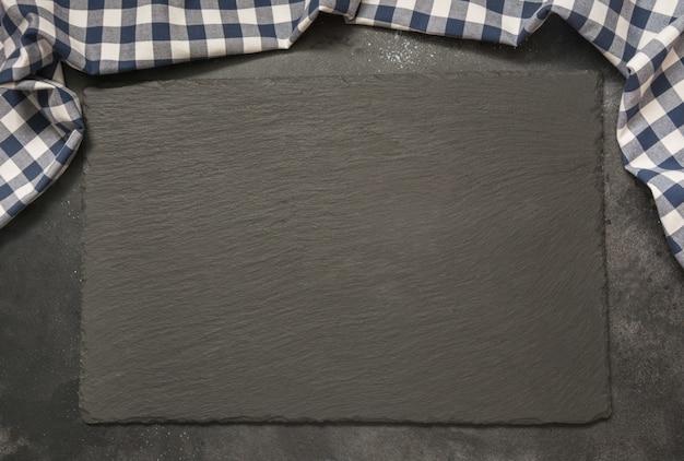 Czarny łupek z kuchennym niebieskim ręcznikiem w kratkę. Premium Zdjęcia