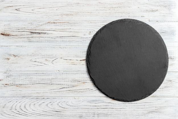 Czarny łupkowy round kamień na drewnianym tle, odgórny widok, kopii przestrzeń Premium Zdjęcia