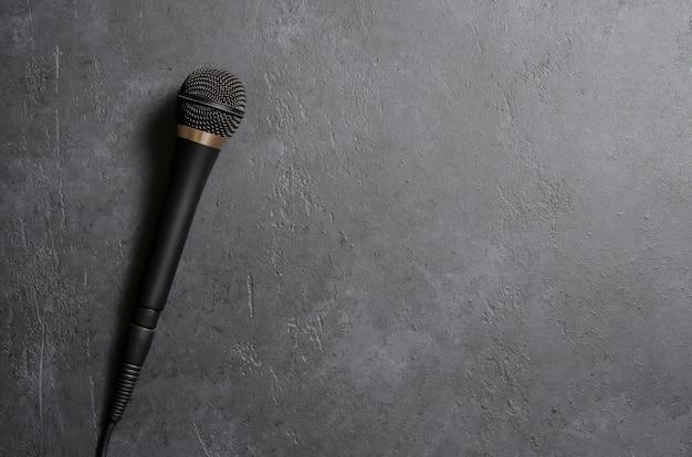 Czarny Mikrofon Na Ciemnym Betonowym Stole. Sprzęt Do śpiewu, Wywiadów Lub Reportaży. Skopiuj Miejsce Premium Zdjęcia