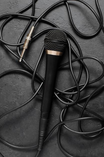 Czarny Mikrofon Na Ciemnym Betonowym Stole. Sprzęt Do śpiewu, Wywiadów Lub Reportaży Premium Zdjęcia