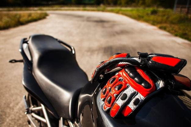 Czarny motocykl z czerwonymi rękawiczkami Darmowe Zdjęcia