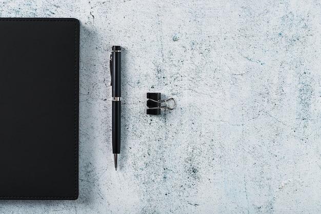 Czarny Notatnik Z Czarnym Długopisem Na Szarym Tle. Widok Z Góry, Minimalistyczna Koncepcja. Wolna Przestrzeń. Premium Zdjęcia