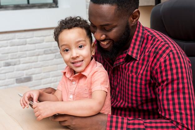 Czarny Ojciec I śliczny Syn Używa Pastylkę Darmowe Zdjęcia