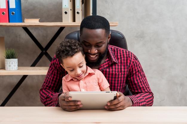 Czarny ojciec i syn używa pastylkę przy stołem Darmowe Zdjęcia