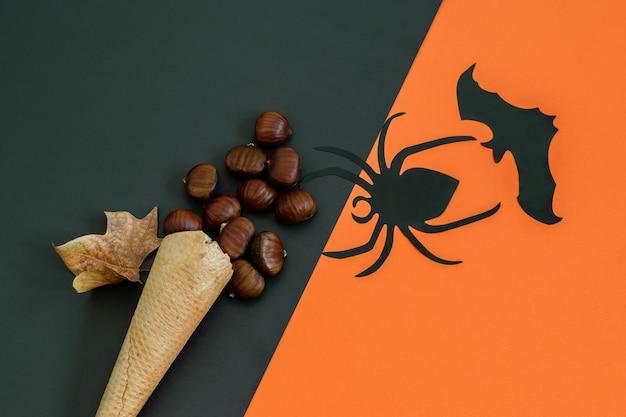 Czarny Pająk, Nietoperz I Wafel W Rożku Z Kasztanami Na Czarno-pomarańczowym Papierze Premium Zdjęcia
