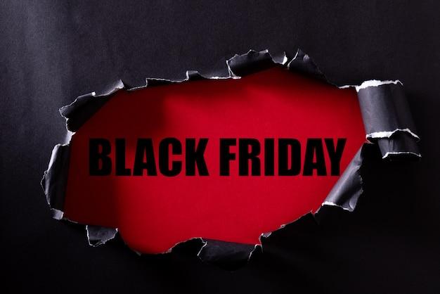Czarny papier rozdarty i tekst czarny piątek na czerwonym. Premium Zdjęcia