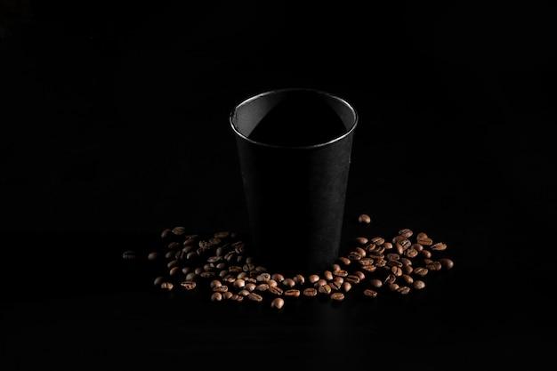Czarny papierowy szkło na czarnym tle. ziarna kawy na ciemnym tle. dzień dobry Premium Zdjęcia