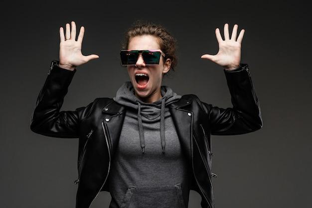 Czarny Piątek Koncepcja. Kaukaska Dziewczyna W Czarnej Skórzanej Kurtce I Szarej Bluzie Machającej Rękami Jest Zaskoczona Na Ciemnoszarym Tle Premium Zdjęcia