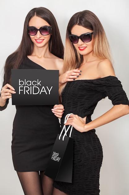 Czarny piątek. wyprzedaż. dwa młodej uśmiechniętej kobiety pokazuje torba na zakupy w czarnym piątku wakacje Premium Zdjęcia