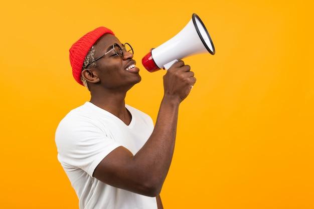Czarny Przystojny Uśmiechnięty Amerykański Mężczyzna W Białej Koszulce Mówi Wiadomości Przez Megafon Na Odosobnionym Pomarańczowym Tle Premium Zdjęcia