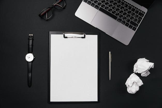 Czarny Pulpit Biurowy Z Białą Kartką Papieru Z Bezpłatną Przestrzenią Do Kopiowania I Długopisem, Laptopem, Okularami, Zegarkiem I Zmiętymi Papierowymi Kulkami. Premium Zdjęcia