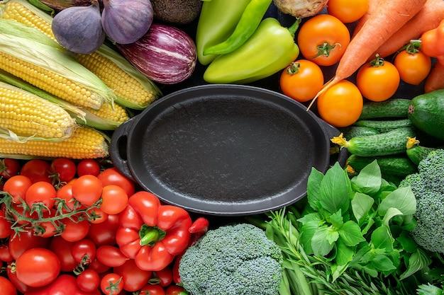 Czarny Pusty Talerz Na Tle świeżych, Jasnych Organicznych Warzyw. Premium Zdjęcia