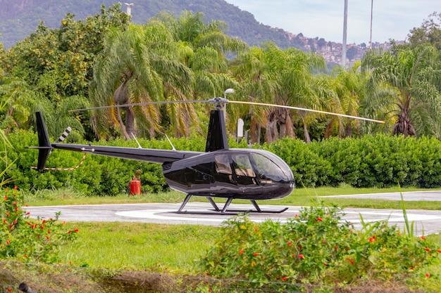 Czarny śmigłowiec Model R44 Raven Ii Zatrzymał Się Na Lądowisku Dla Helikopterów W Lagunie Rodrigo De Freitas W Rio De Janeiro. Premium Zdjęcia