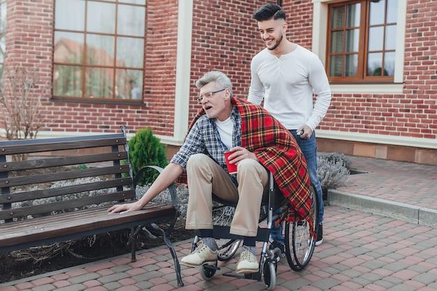 Czas Dla Rodziny. Syn Pomaga Swojemu Starszemu Ojcu Na Wózku Inwalidzkim W Ogrodzie Opieki. Premium Zdjęcia