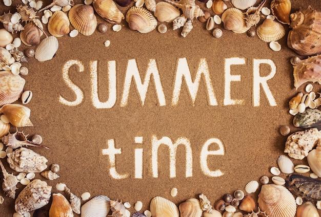 Czas Letni Jest Zapisywany Na Piasku W Ramce Muszli Morskich. Premium Zdjęcia