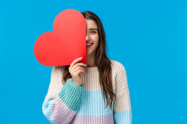 Czas Powiedzieć, że Cię Kocham. Wesoła Marzycielska I śliczna Caucasian Brunetki Kobieta Przykrywa Pół Twarzy Wielkim Czerwonym Sercem, Uśmiecha Się, Wyraża Uczucia I Sympatię W Walentynki, Otrzymuje Uroczy Prezent Premium Zdjęcia