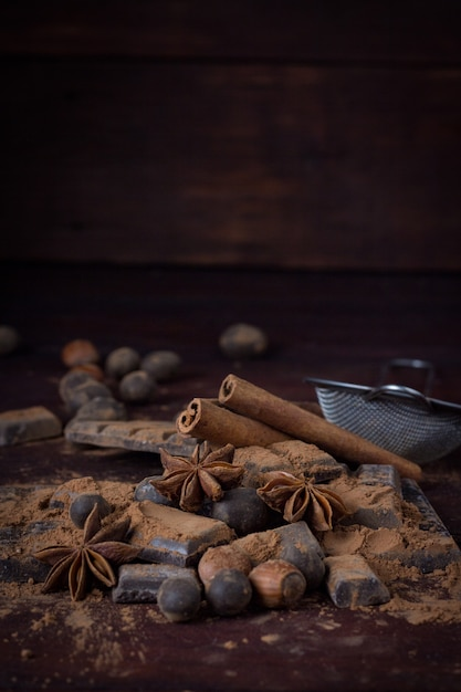 Czekolada, Przyprawy, łyżka Z Kakao, Metalowy Sitko, Orzech Laskowy Na Ciemnej Powierzchni Drewnianej. Skopiuj Miejsce Premium Zdjęcia